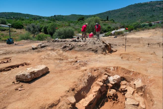 Au 1er rang, une sépulture en coffre de pierres et au 2ème plan, les archéologues de l'INRAP fouillent l'empierrement dont la fonction est jusqu'alors indéterminée