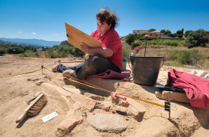 Une archéologue réalise le relevé d'une couverture en suspens (dalle de sol en terre cuite)