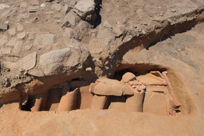 Tombe en bâtière décorée de symboles en traces digitées situées sous l'empierrement