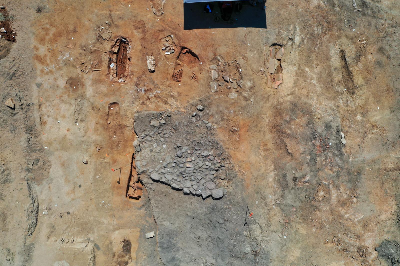 Empierrement en partie fouillé sous lequel apparait la tombe en bâtière décorée